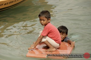 Anak laut swimming and playing in the sea, right outside their homes