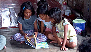 Kamisa and her cousins looking at picture books given by THF