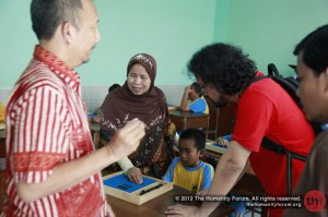 A teacher gives a demo to THF volunteer on how braille math works.